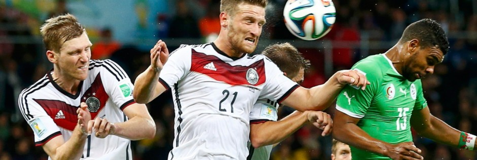 Germany's Mertesacker and Mustafi jump for the ball with Algeria's Soudani during their 2014 World Cup round of 16 game at the Beira Rio stadium in Porto Alegre