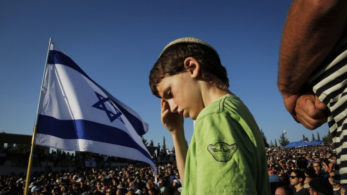 An Israeli boy attends the joint funeral of three Israeli teens who were abducted and killed in the occupied West Bank, in the Israeli city of Modi'in