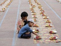 Children sit next to food placed for Muslims before the Iftar meal, during the holy fasting month of Ramadan, at the Jama Masjid in the old quarters of Delhi