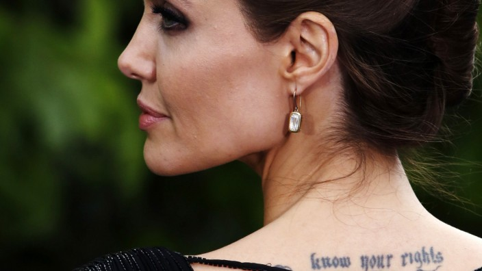 Actress Angelina Jolie displays her tattoo as she arrives for a special Maleficent Costume Display at Kensington Palace in London