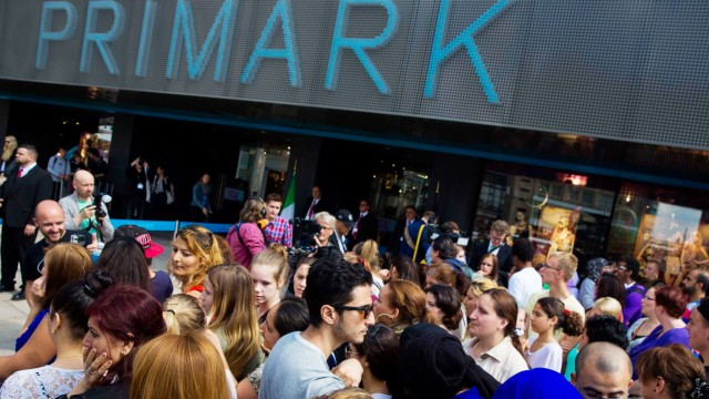 People line up outside a store of clothing retailer Primark before its opening in Berlin