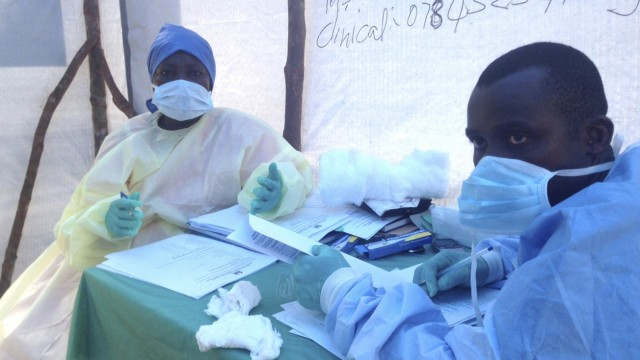 Government health workers are seen during the administration of blood tests for the Ebola virus in Kenema