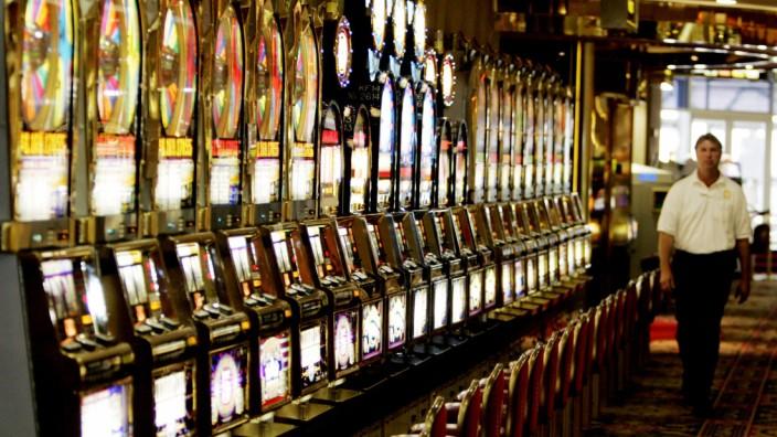 Employee walks past slot machines on an empty casino floor at Caesars in Atlantic City New Jerse