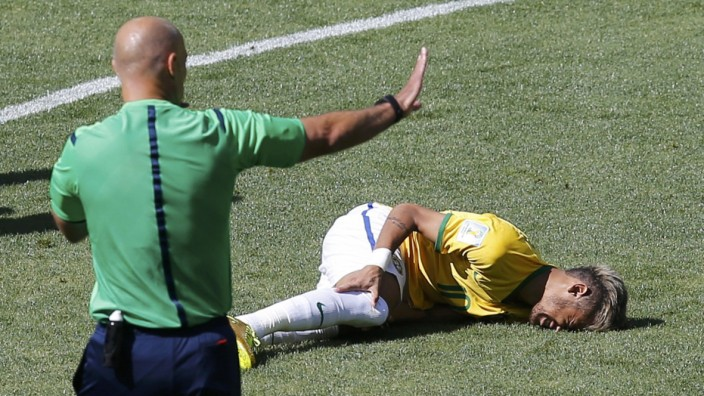 Brazil's Neymar lies injured on the ground as referee Howard Webb of England gestures during their 2014 World Cup round of 16 game against Chile at the Mineirao stadium in Belo Horizonte