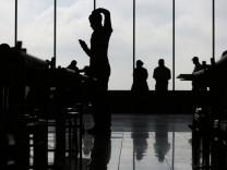 Menschen mit Smartphones warten am Curitiba Airport, Brasilien