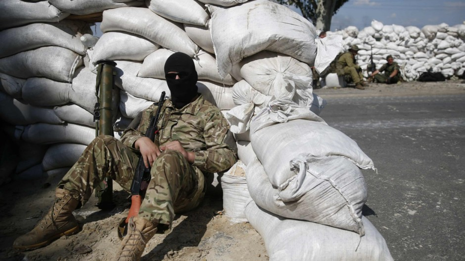 Pro-Russian separatist fighters from the so-called Battalion Vostok (East) wait behind sandbag walls at a checkpoint on the outskirts of Donetsk