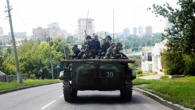 Pro-Russian separatist fighters from the so-called Battalion Vostok (East) travel on an armoured vehicle in Donetsk