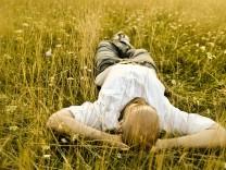 Mann liegt im Gras