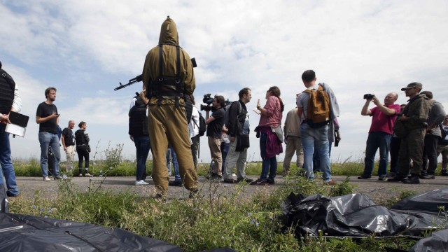 OSCE monitors and journalists walk as pro-Russian separatist stands on guard near bodies at crash site of Malaysia Airlines Flight MH17, near settlement of Grabovo