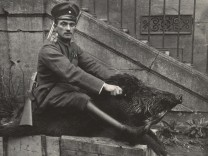 A German Air Force Officer sits astride a dead boar outside a house where he was stationed near the Western Front, in this 1918 handout picture