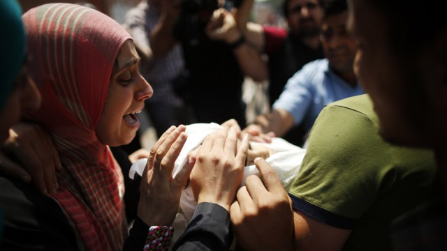 The aunt of Palestinian boy Mohammed Ayad, who medics said was killed during heavy Israeli shelling, mourns as she looks at his body during his funeral in Gaza City