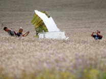 Malaysian air crash investigators take photos of the crash site of Malaysia Airlines Flight MH17