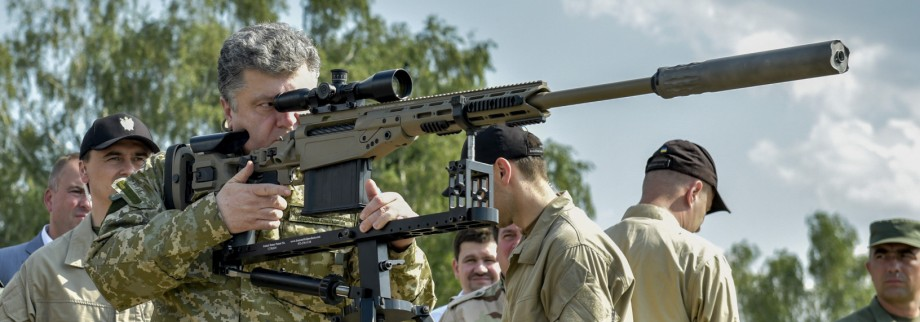 Ukraine's President Poroshenko aims a rifle during his visit to a demonstration of new weapons for the Ukrainian armed forces at a military base outside Kiev