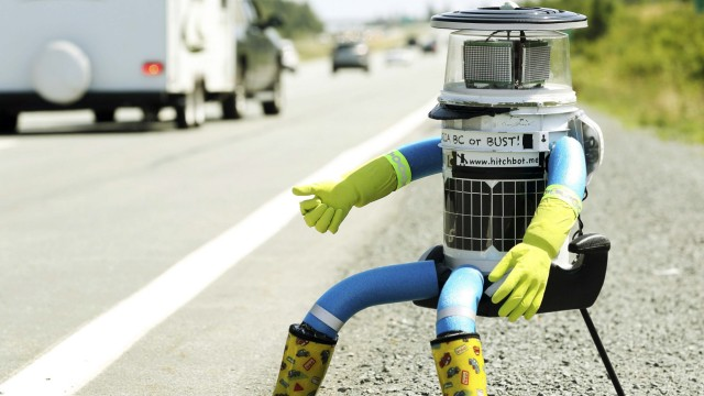 The anthropomorphic robot named hitchBOT sits on the shoulder of Highway 102 to begin its 6000 kilometer cross country journey outside of Halifax