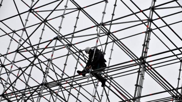 Hohes Risiko: Ein Bauarbeiter steht auf dem Gerüst eines temporären Gebäudes an der Pinakothek der Moderne in München.
