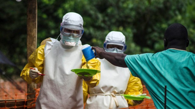 Medical staff working with Medecins sans Frontieres prepare to bring food to patients kept in an isolation area at the MSF Ebola treatment centre in Kailahun