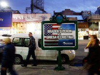 People walk past a poster placed on an advertising board that reads 'Yesterday, Braden or Peron - Today: Griesa or Cristina', in Buenos