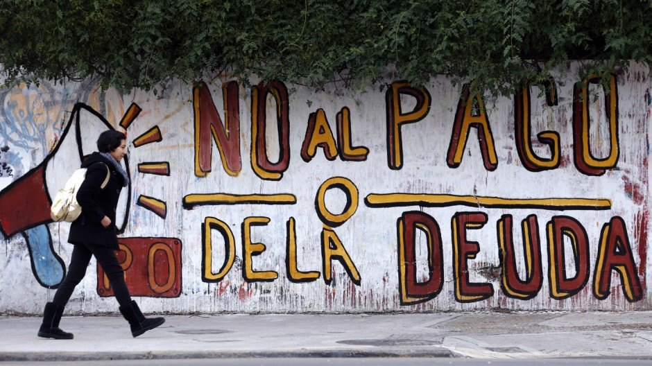 A woman walks past a graffiti in Buenos Aires