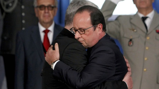 France's President Hollande and German President Gauck embrace as they pay their respects in the crypt of the National Monument of Hartmannswillerkopf in Wattwiller