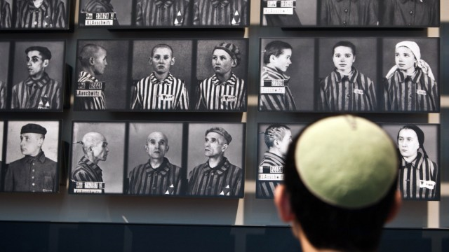 A visitor looks at pictures of Holocaust victims at Yad Vashem's Holocaust History Museum in Jerusalem