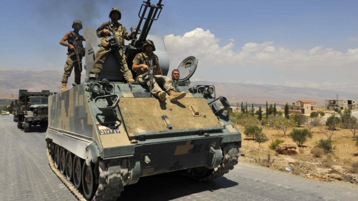 Lebanese army soldiers on armoured carriers and military vehilces advance towards Sunni Muslim border town of Arsal, in eastern Bekaa Valley as part of reinforcements