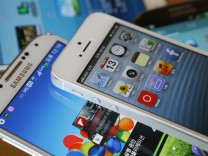 File photo illustration of an Apple's iPhone 5 and a Samsung Electronics' Galaxy S4 taken in Seoul
