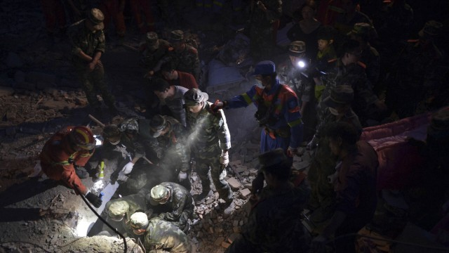 Paramilitary policemen use flashlights to search for the body of a boy at night after an earthquake hit the Longtoushan township of Ludian county