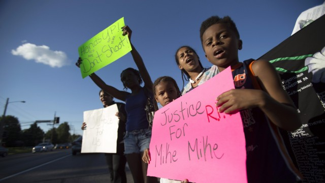 Lisa Kemp chants with children Xavier and Zyniyah while protesting the death of black teenager Michael Brown in Ferguson