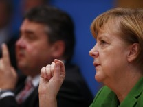 Party leaders German Chancellor Merkel of the CDU and Gabriel of the SPD attend a news conference after signing a preliminary agreement, which has still to be approved by the members of the SPD, in the Bundespressekonferenz