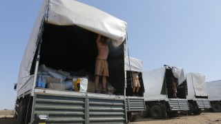 Drivers of a Russian convoy of trucks carrying humanitarian aid for Ukraine show the contents of their trucks at a camp near Kamensk-Shakhtinsky
