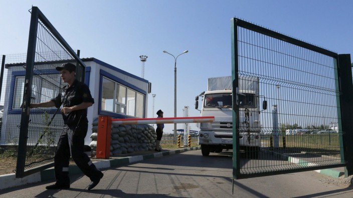 A Russian border guard opens a gate in front of a truck from a convoy that delivered humanitarian aid for Ukraine on its return to Russia at border crossing point 'Donetsk' in Russia's Rostov Region
