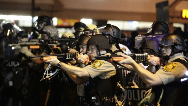 Police officers point their weapons at demonstrators protesting against the shooting death of Michael Brown in Ferguson, Missouri