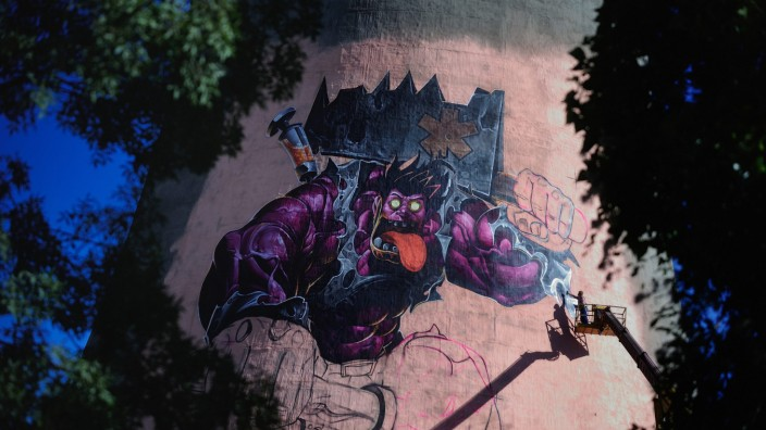 An artist paints his graffiti of the villain Dr. Mundo in Sofia