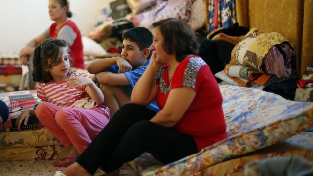 An Iraqi Christian family from Mosul, who fled from violence in their country, sits at the Latin Patriarchate Church in Amman