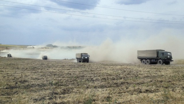 Military trucks travel through the steppe near the village of Krasnodarovka