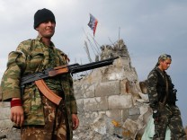 Pro-Russian separatists walk at a destroyed war memorial on Savur-Mohyla, a hill east of the city of Donetsk