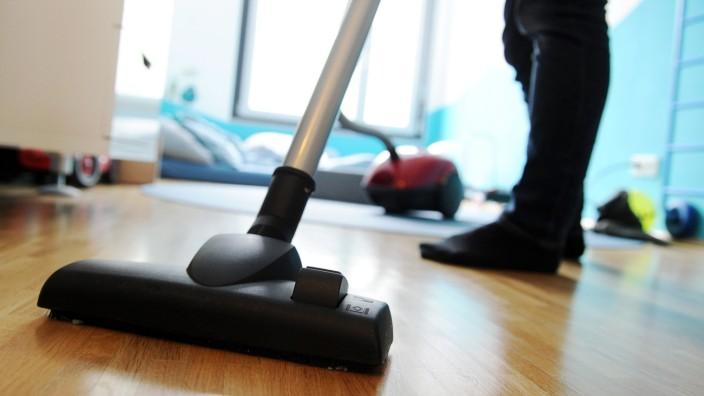 Eine Person saugt Staub auf altmodische Weise. Dank Staubsauger-Robotern könnte das bald überflüssig sein.