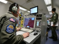 A controller sits at screens aboard NATO AWACS aircraft during surveillance flight over Romania from AWACS air base in Geilenkirchen