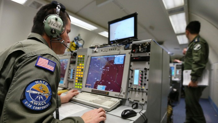 A controller sits at screens aboard NATO AWACS aircraft during surveillance flight over Romania from AWACS air base in Geilenkirchen