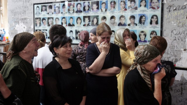 People mourn inside School Number One during a ceremony commemorating the victims of the 2004 hostage crisis in the southern Russian town of Beslan