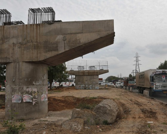 File photo shows vehicles travelling past a Delhi-Jaipur national highway flyover under construction at Manesar in Haryana