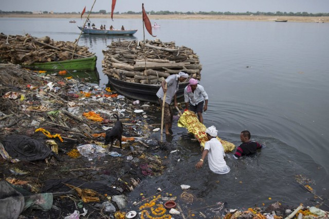 Relatives immerse a body in the river Ganges prior to cremation in Varanasi