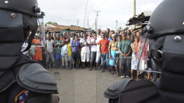 Liberian security forces stand in front of protesters after clashes at West Point neighbourhood in Monrovia