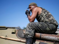 A Ukrainian serviceman smokes as he sits on an armoured vehicle near Kramatorsk