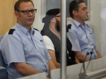 Defendant identified as Marco G. sits between security officers at the higher regional court in Duesseldorf