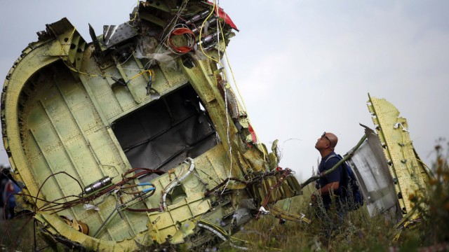 File photo of a Malaysian air crash investigator inspecting the crash site of Malaysia Airlines Flight MH17, near the village of Hrabove
