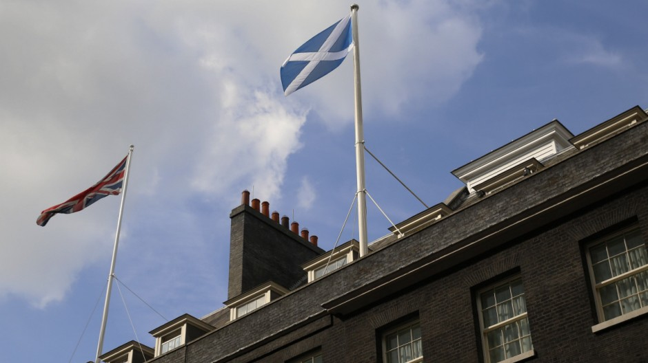 A Scottish Saltire flag flies alongside a Union flag on top of 10 and 11 Downing Street in London