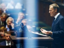 Poland's PM Tusk gestures as he delivers a speech at parliament in Warsaw