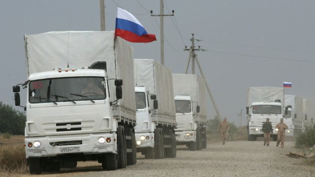 A Russian convoy of trucks carrying humanitarian aid for Ukraine are parked by the side of a road near Kamensk-Shakhtinsky