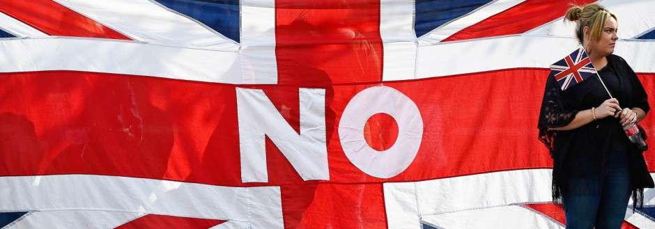A woman stands by a Union flag as she watches a pro-Union rally in Edinburgh, Scotland